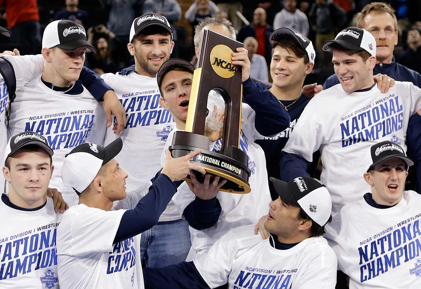 Penn State's Zain Retherford is handed the team's trophy as it poses for a photo after winning the NCAA Division I wrestling championships in New York.