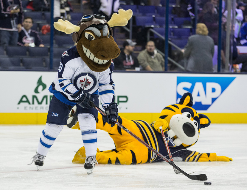 Winnipeg mascot Mick E. Moose skates with a big grin on his face as he leaves Buffalo Sabres mascot Sabretooth helpless on the ice during the inaugural NHL All-Star Mascot Showdown.