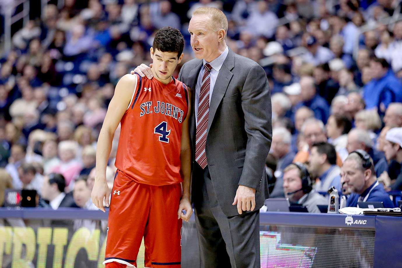 Chris Mullin, the head coach of the St. John's Red Storm, gives instructions to Federico Mussini during the game against the Xavier Musketeers at Cintas Center in Cincinnati.