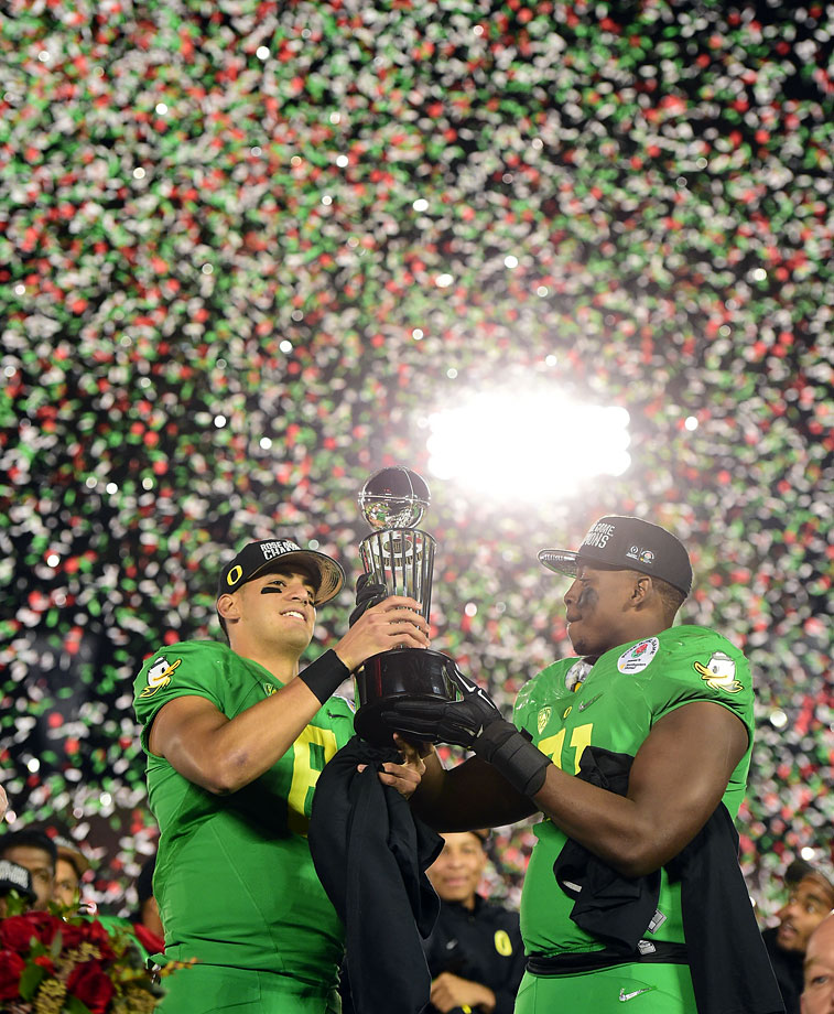 Marcus Mariota and Tony Washington hold the Leishman Trophy after Oregon's victory.