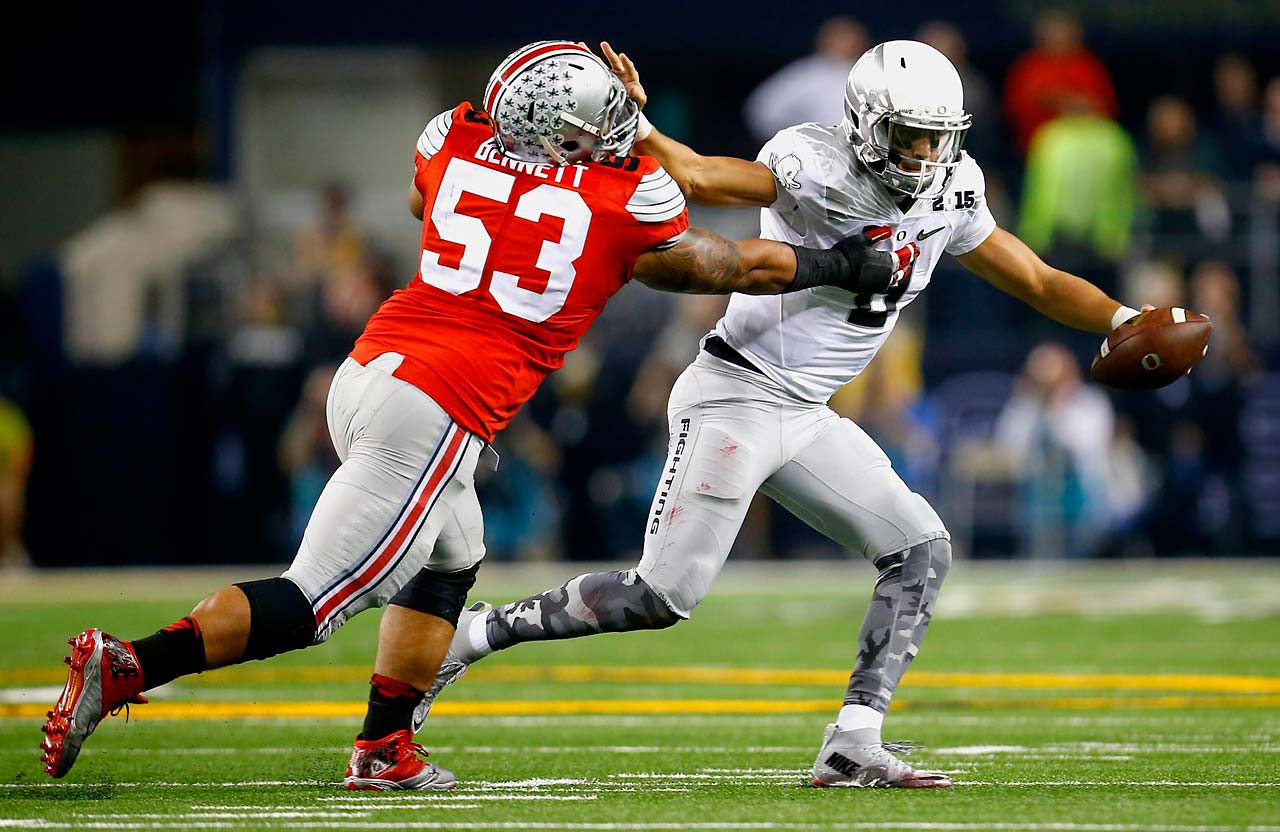 Oregon quarterback Marcus Mariota tries to stiff arm Ohio State linebacker Michael Bennett (53).