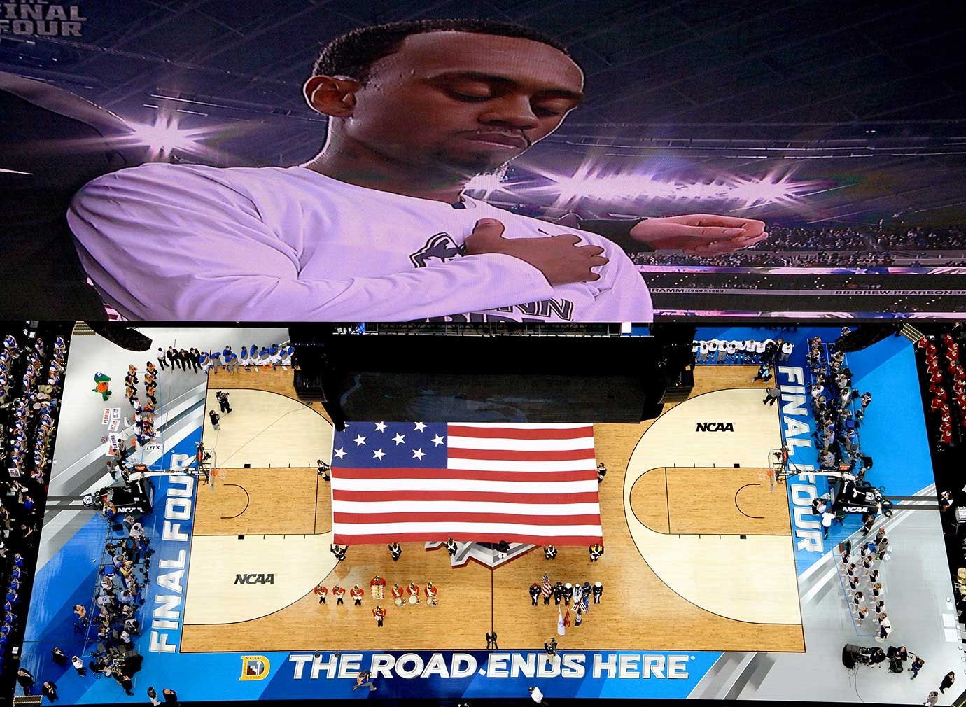 A UConn player on the screen at AT&T Stadium in Arlington with the USA flag unfurled below prior to a 2014 Final Four game between the Huskies and Florida.