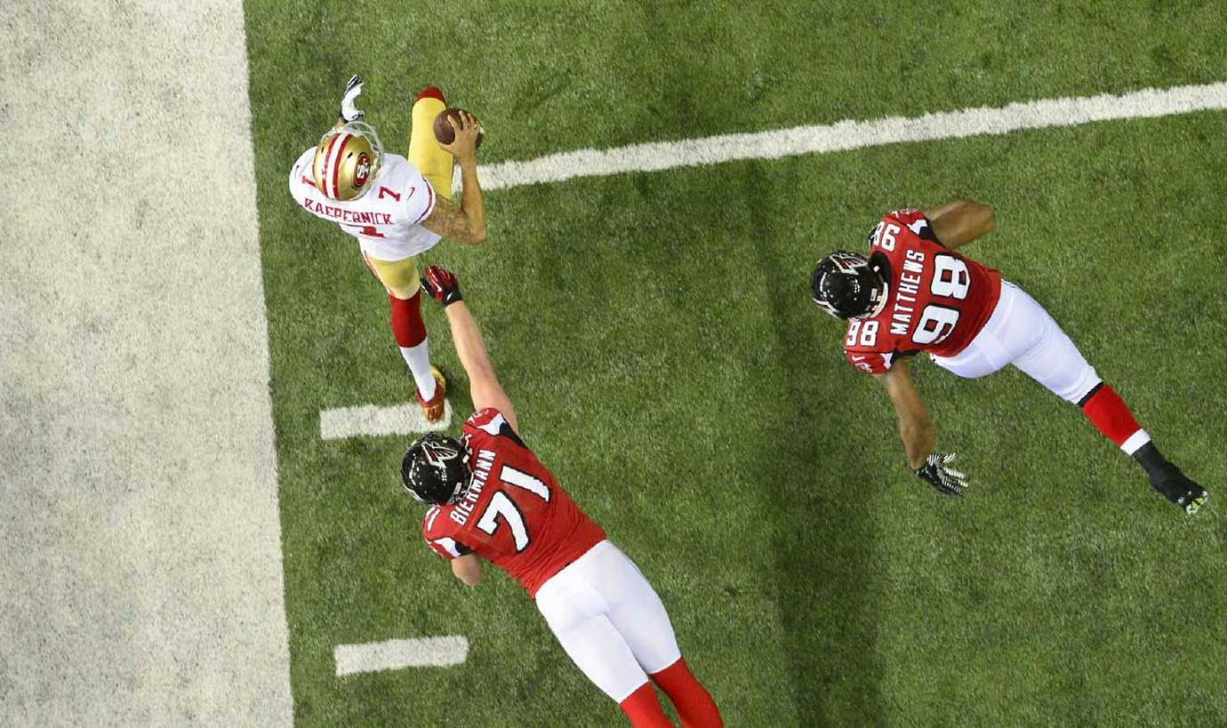 San Francisco quarterback Colin Kaepernick escapes Atlanta defenders during a 2013 playoff game in the Georgia Dome.
