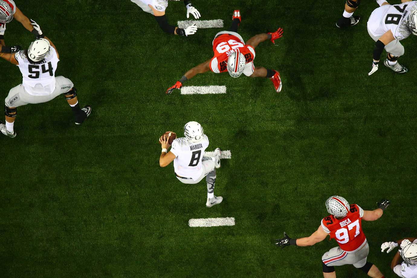 Oregon quarterback Marcus Mariotta gets pressured by an Ohio State's Tyquan Lewis in the 2015 college football national title game.