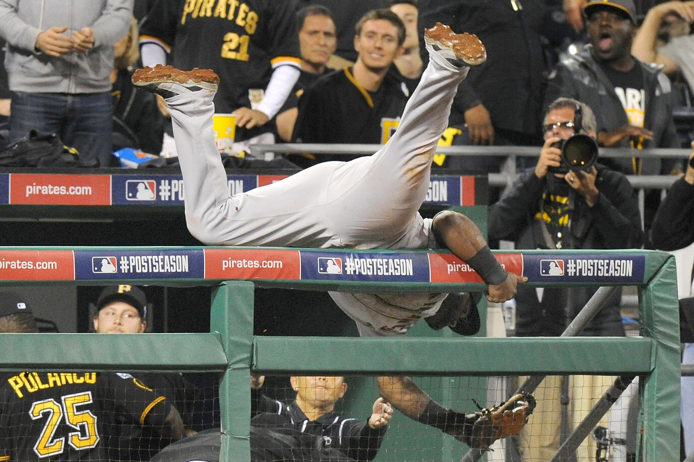 San Francisco Giants third baseman Pablo Sandoval flips over the dugout railing after making a catch against the Pirates.