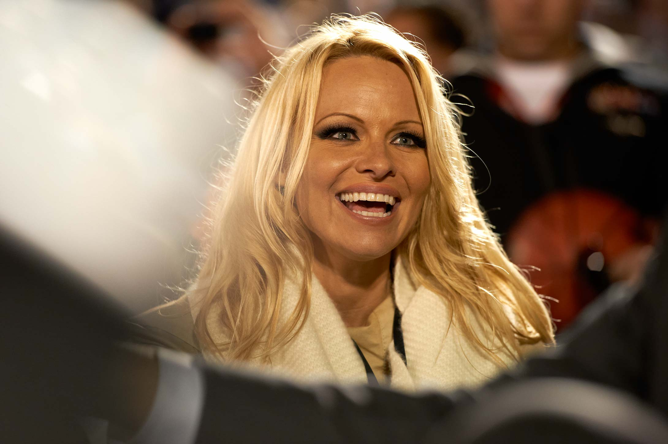 Pamela Anderson seated courtside at the 2011 game between Michigan State and North Carolina aboard the USS Carl Vinson (CVN-70) aircraft carrier docked in Naval Air Station North Island.