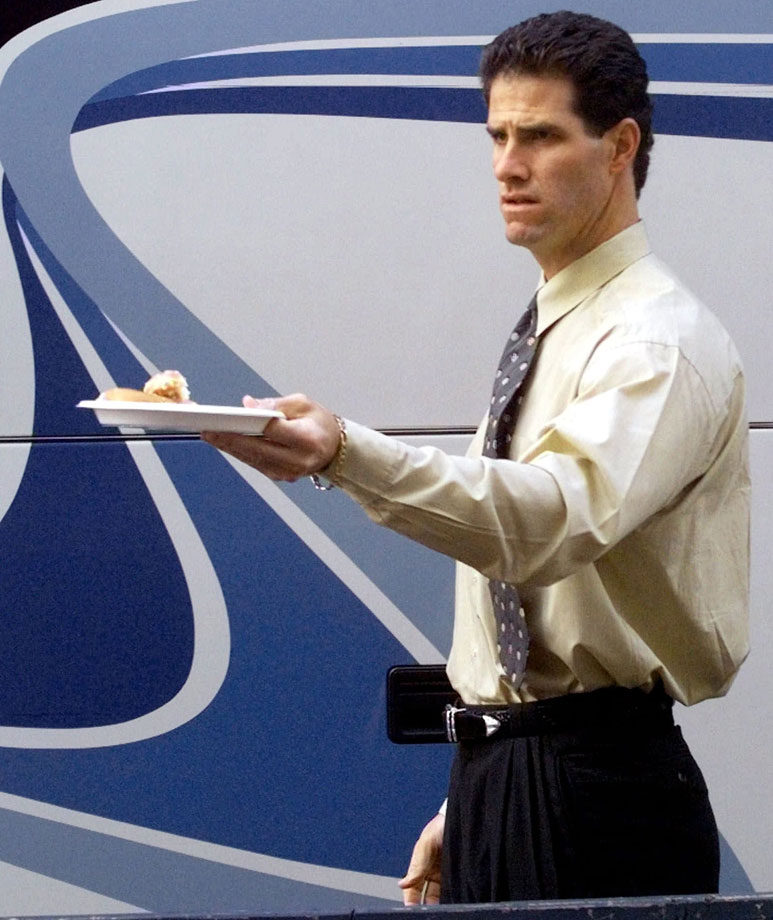 New York Yankees outfielder Paul O'Neill offers some doughnuts to his teammates outside of Yankee Stadium on Oct. 22, 1999 in New York City, before traveling to Atlanta for Game 1 of the World Series.
