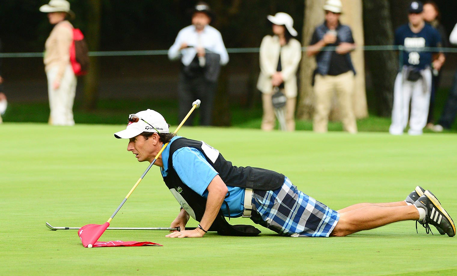 Paula Creamer's caddie gets down to read a putt at the Lorena Ochoa Invitational Golf Tournament in Mexico.