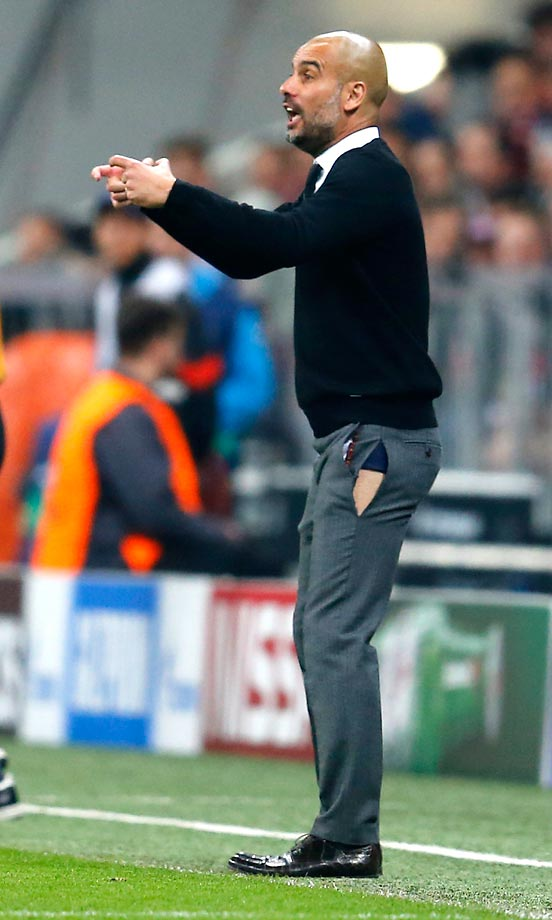 With his pants torn, Bayern's coach Pep Guardiola gestures towards the field during a match against FC Porto at the Allianz Arena in Munich.