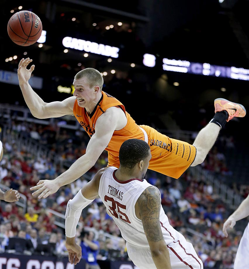 Phil Forte III of Oklahoma State is upended by TaShawn Thomas of Oklahoma. Oklahoma won 64-49.