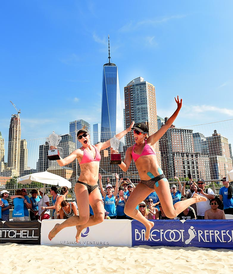 "Emily Day (left) and Jennifer Kessy with their victory jump in front of Emily Day's ""entourage"" (blue shirts) and the New York City skyline."