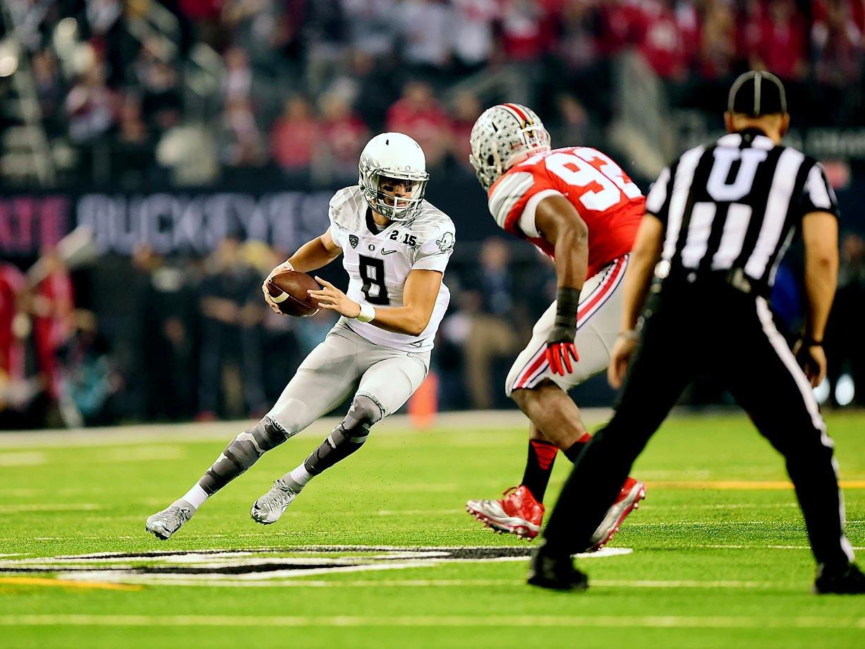 Oregon quarterback Marcus Mariota tries to evade Ohio State defensive lineman Adolphus Washington. Mariota threw for 333 yards in the Ducks' loss.