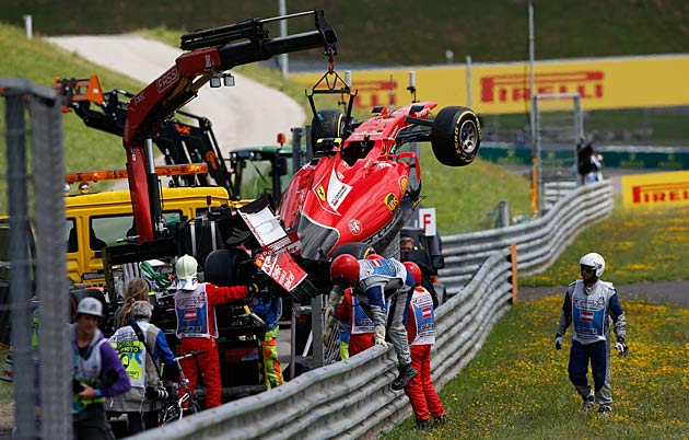Kimi Raikkonen's car is retrieved after he crashed at the 2015 GP of Austria.