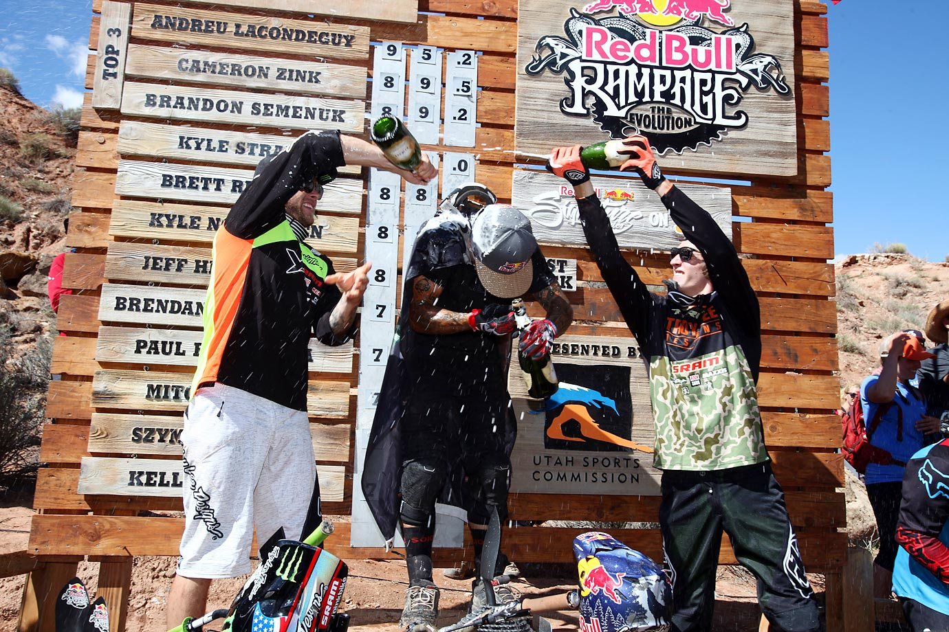 Cameron Zink, Andreu Lacondeguy, and Brandon Semenuk celebrate on the podium.