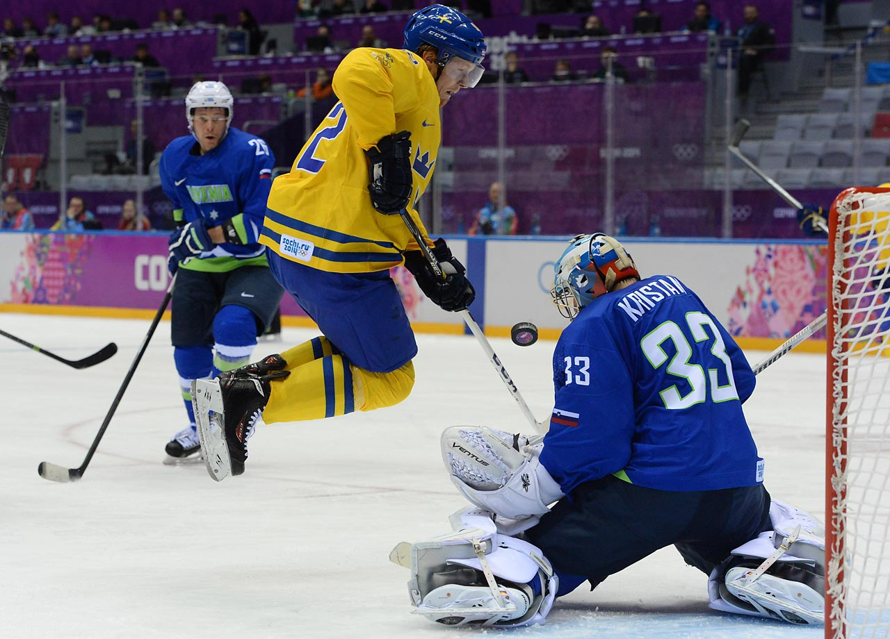 Slovenian goaltender Robert Kristan deflects a shot by Swedish forward Gabriel Landekog in a quarterfinal game. Sweden advanced with a 5-0 victory.
