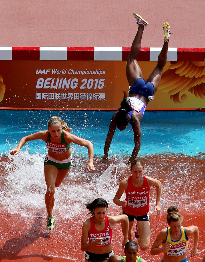 Rolanda Bell of Panama takes a spill during the steeplechase in Beijing.