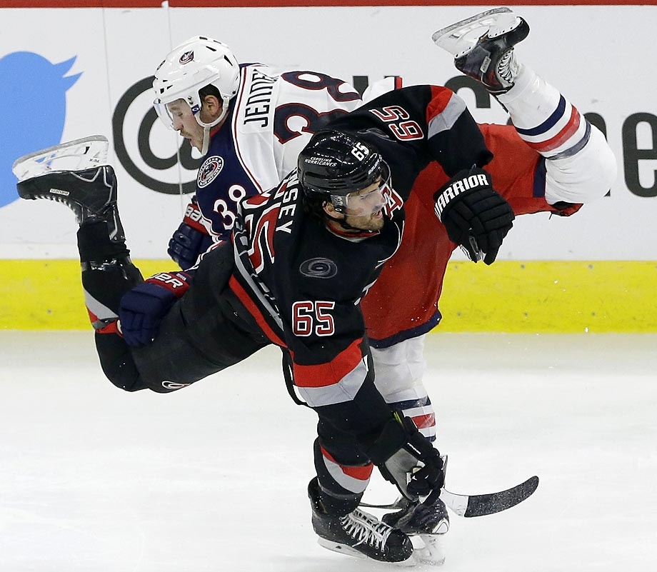 Carolina Hurricanes defenseman Ron Hainsey gets tangled with Columbus Blue Jackets forward Boone Jenner.