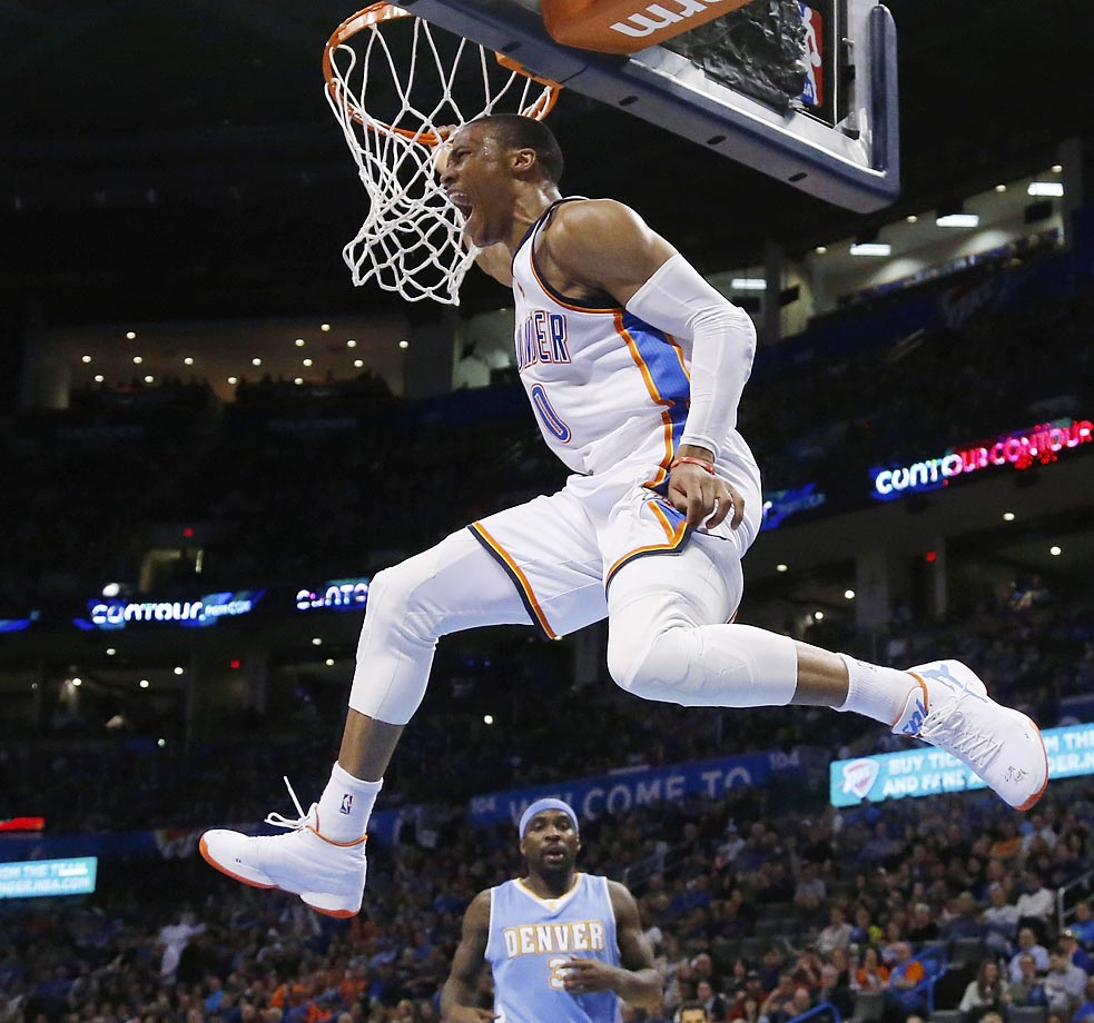 Oklahoma City Thunder guard Russell Westbrook hangs from the basket in front of Denver Nuggets guard Ty Lawson  following a dunk.