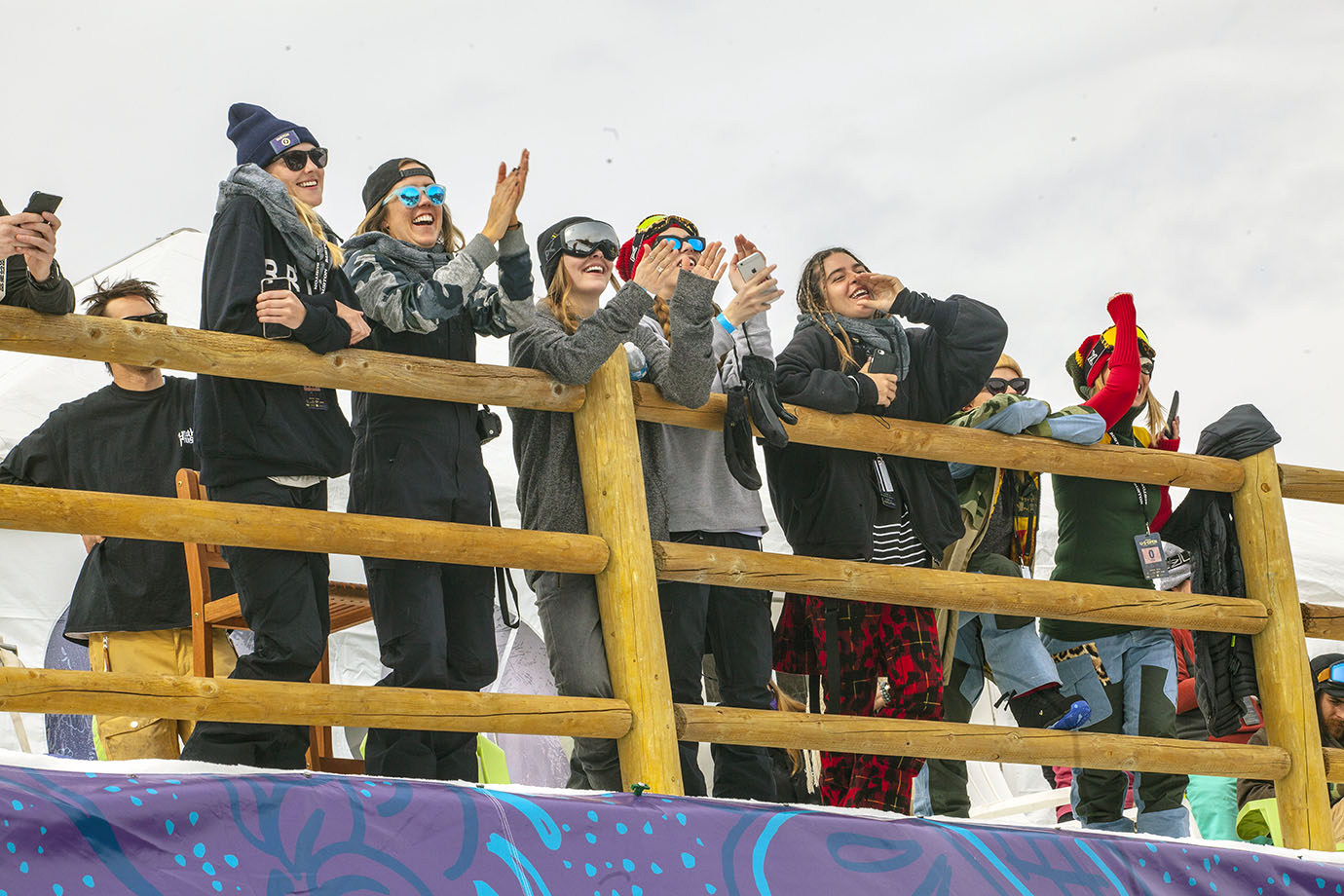 Members of Burton cheer on participants in the women's Slopestyle final on Friday morning.