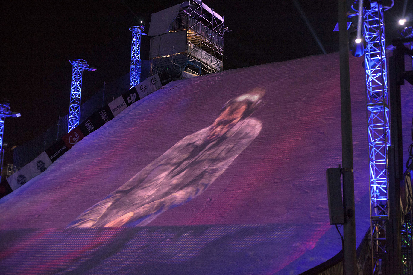Kaskade's musical performance in between rounds is projected onto the face of the jump landing, marrying the two primary elements of Air+Style: music and snow.