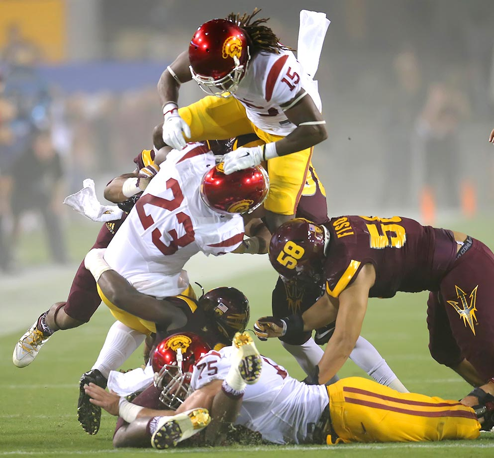 Issac Whitney of USC knees teammate Tre Madden in the head, knocking him to the ground. The Trojans defeated ASU 42-14.