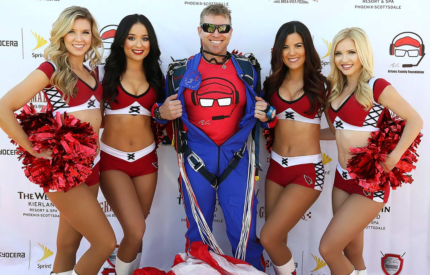 Arizona Cardinals cheerleaders pose with a parachute jumper as he shows off the new Arians Family Foundation logo in Superman fashion at the 3rd Annual Arians Family Foundation Arizona Celebrity Golf Classic in Scottsdale, Ariz.