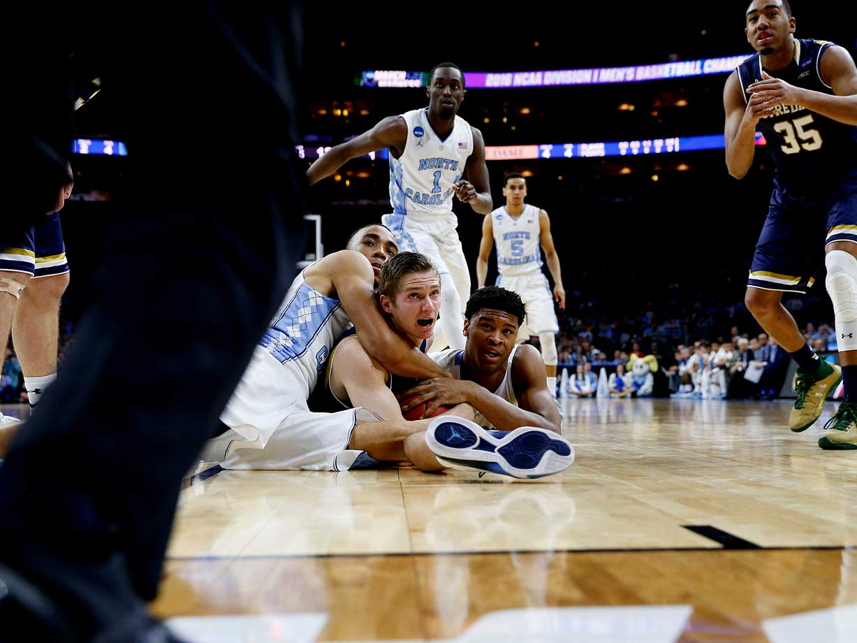 Isaiah Hicks (4) of North Carolina and Rex Pflueger (0) of Notre Dame wrestle for the ball in a game in which the Tar Heels used a 12-0 run that gave them a 63-52 lead with 9:19 to play.
