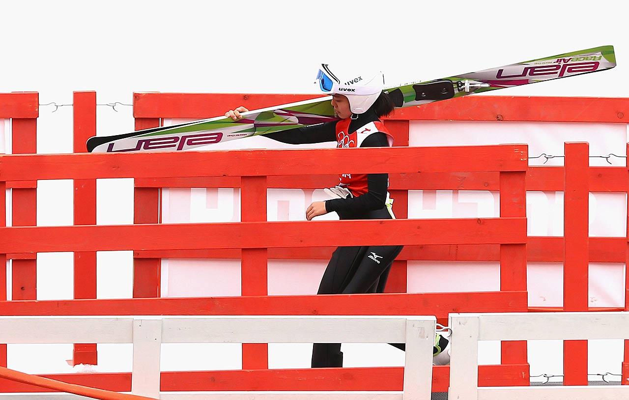 Sara Takanashi of Japan walks to the chairlift during the Ladies' Normal Hill Individual Ski Jumping training.