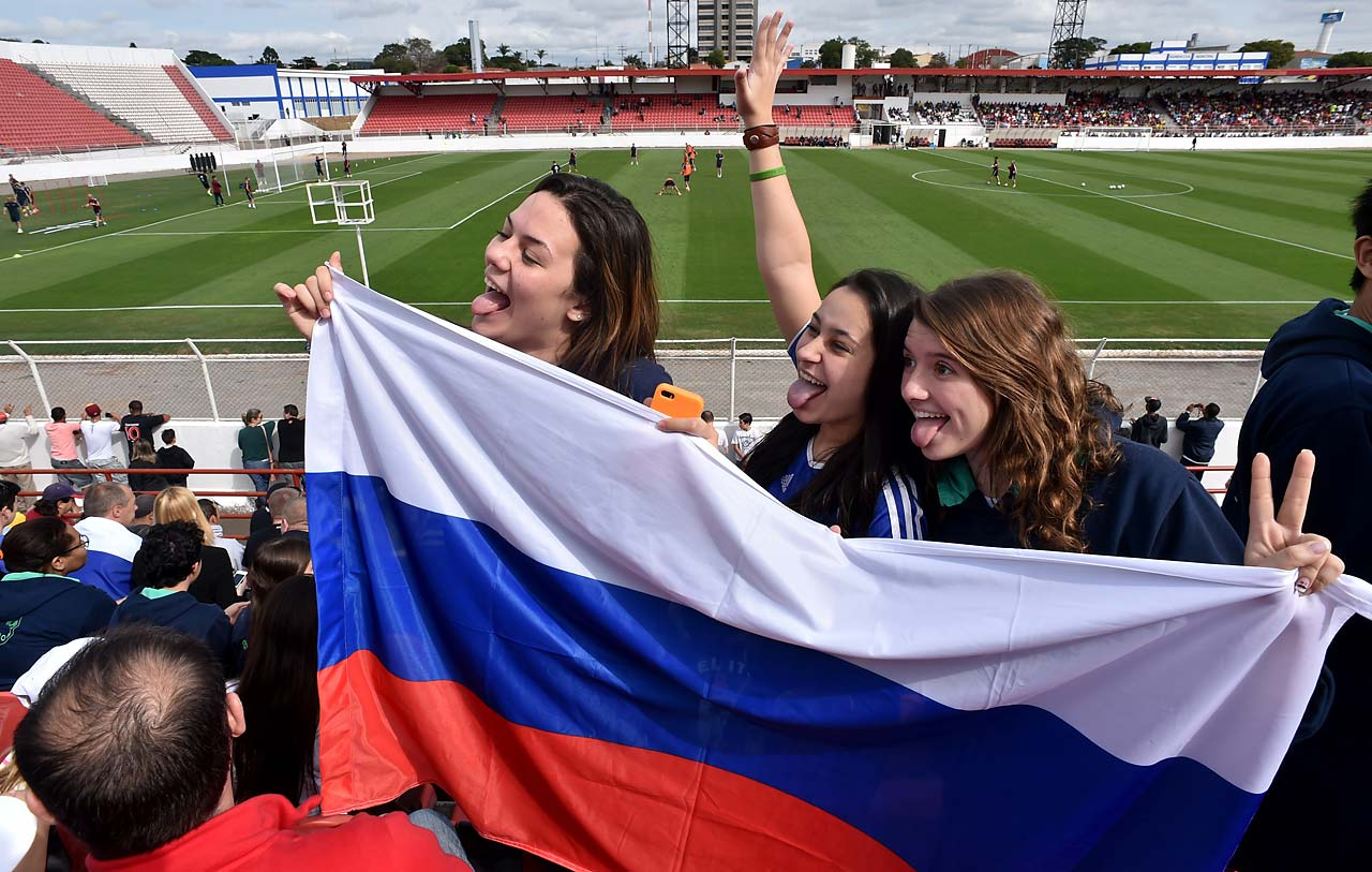 Supporters pose with a national flag as members of Russia's national football team take part in a training session at Estadio Novelli Junior in Itu on the outskirts of Sao Paulo on June 10.
