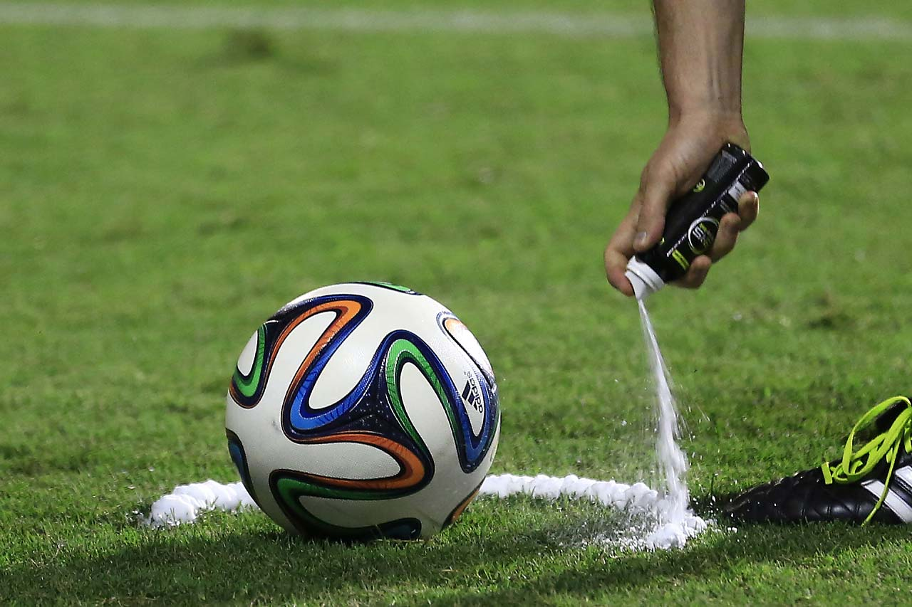 In this  June 6, 2014, photo, a referee uses vanishing spray during a referee's training session in Rio de Janeiro, Brazil. Referees will use vanishing spray during 2014 World Cup to stop defensive walls creeping forward at free-kicks. The international soccer tournament is set to begin in a few days, with Brazil and Croatia competing in the opening match on June 12.