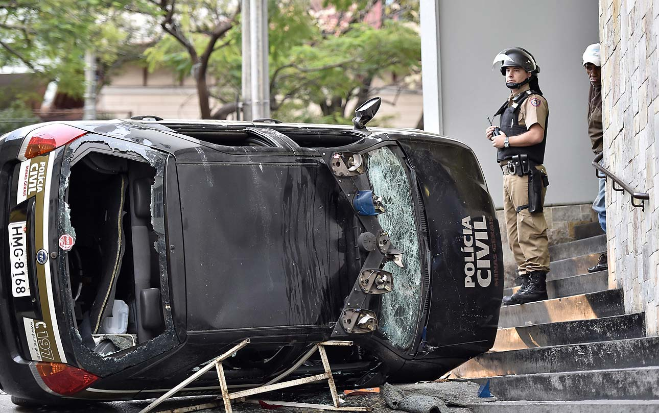 A police officer stands next to a destroyed police car during a violent demonstration at the 2014 World Cup in the center of Belo Horizonte , Brazil, on June 12, 2014. Protesters clashed with police at a rally against the World Cup, demanding better public services and protesting the money spent on the soccer tournament.