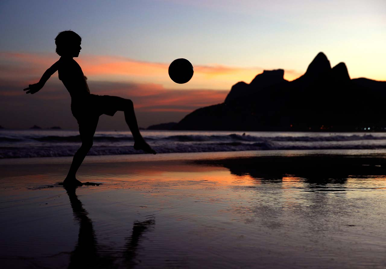 A young boy juggles a football on Ipanema Beach on Sunday, June 8, as the 2014 FIFA World Cup nears.