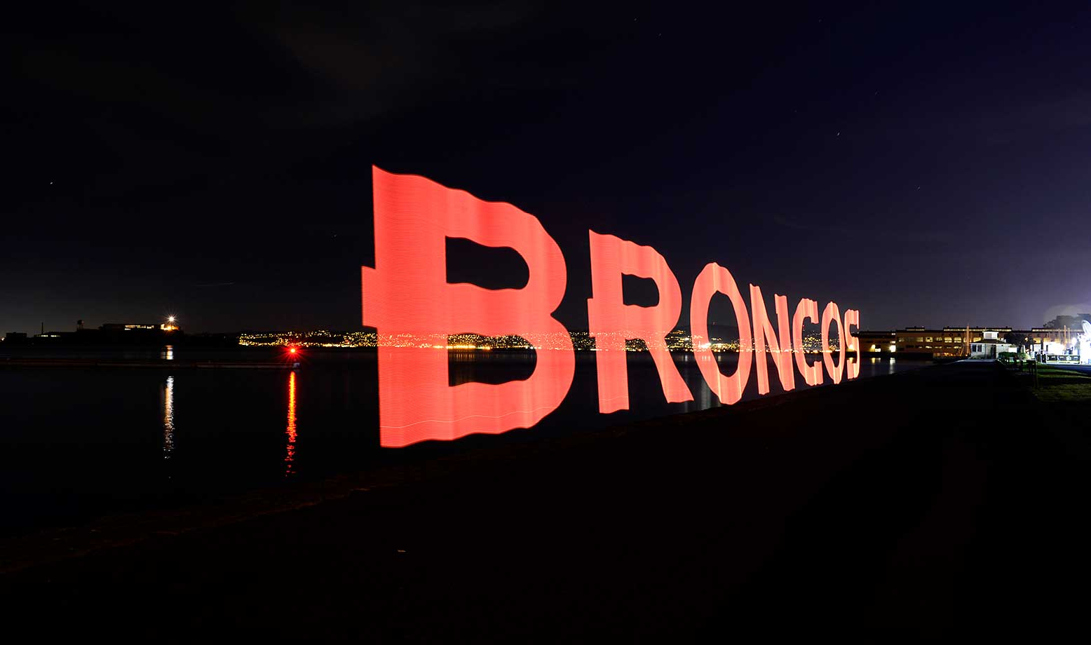 A still photograph of the Denver Broncos logo painted with light using a Pixelstick during a 30 second long exposure. Alcatraz in background.