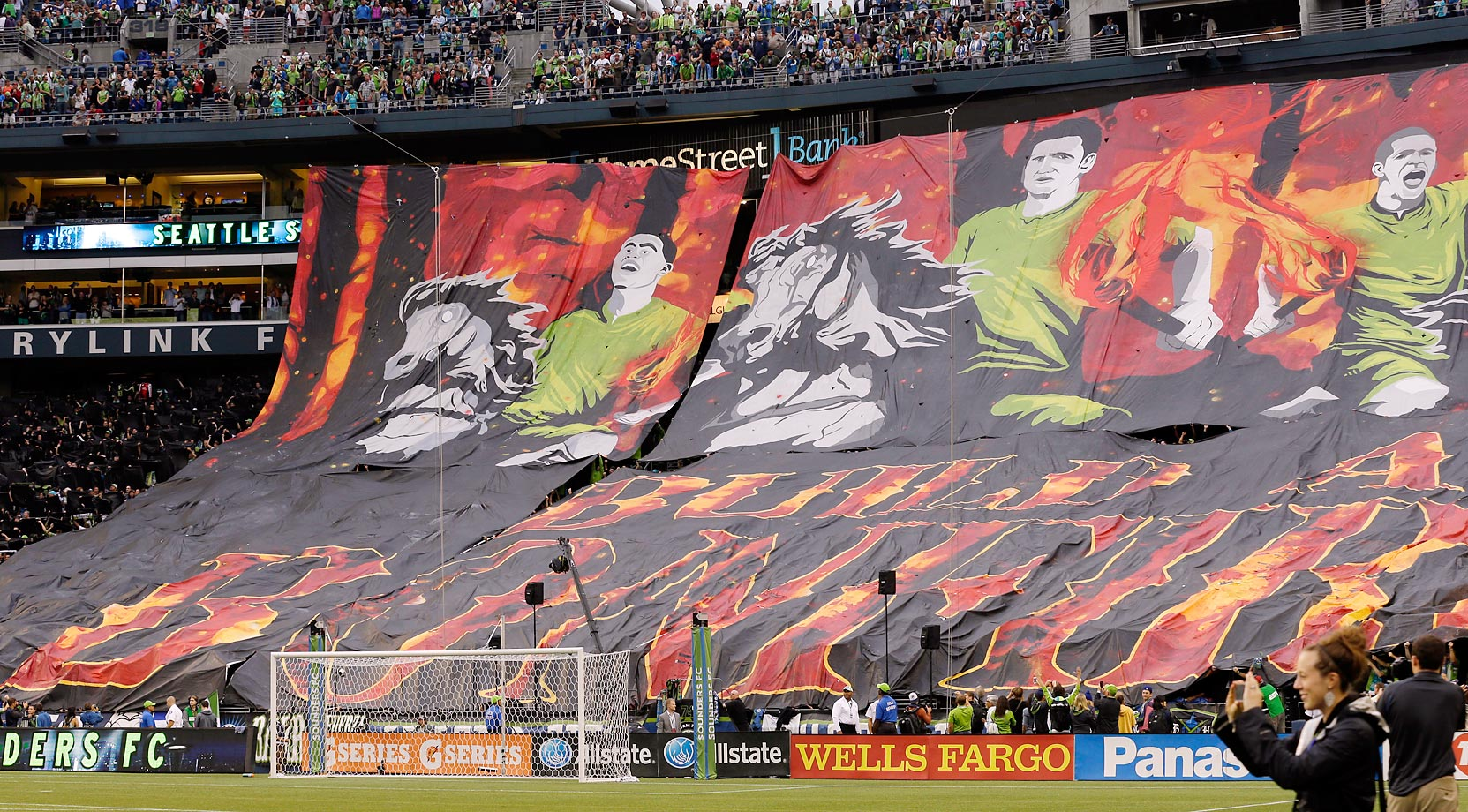 "Seattle Sounders fans unveil a tifo inspired from the ""Build a Bonfire"" chant, featuring Sounder players holding torches on horseback ahead of a game against the Portland Timbers."