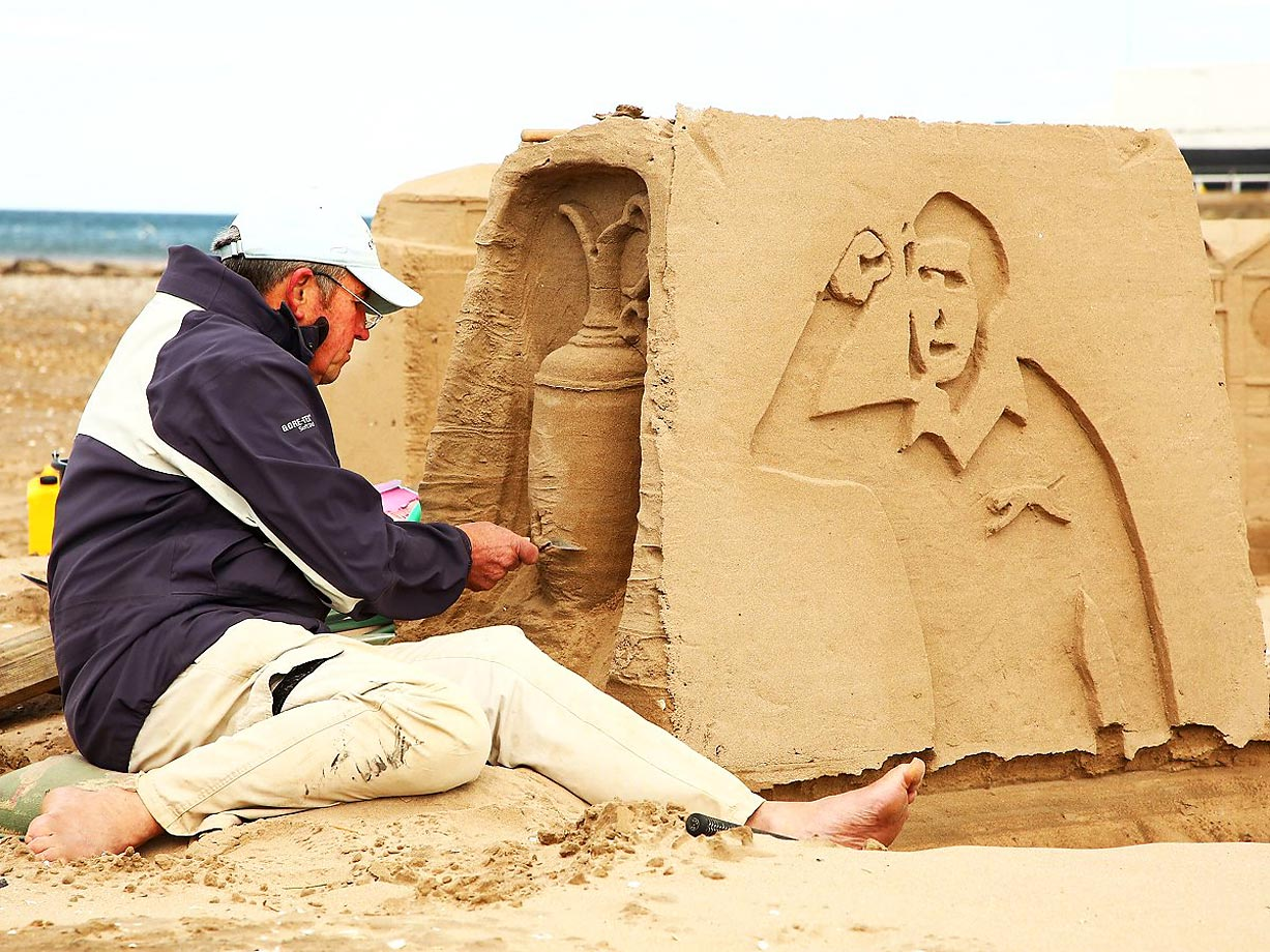 A fan putting finishing touches on a sand sculpture of Seve Ballesteros at the British Open.