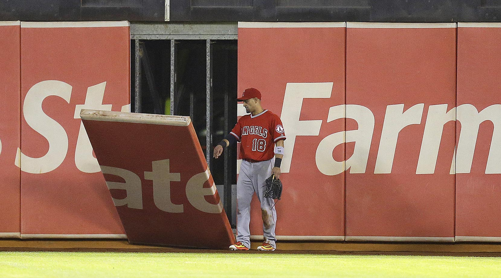 Shane Victorino of the Los Angeles Angels watches a piece of the leftfield wall fall off after he ran into it while trying to field a ball.
