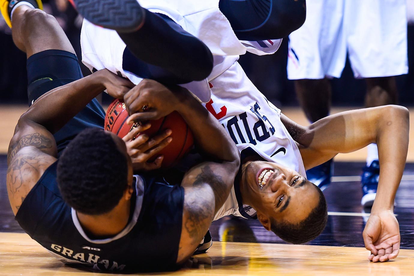 ShawnDre' Jones of Richmond fights for the ball against Treveon Graham of Virginia.