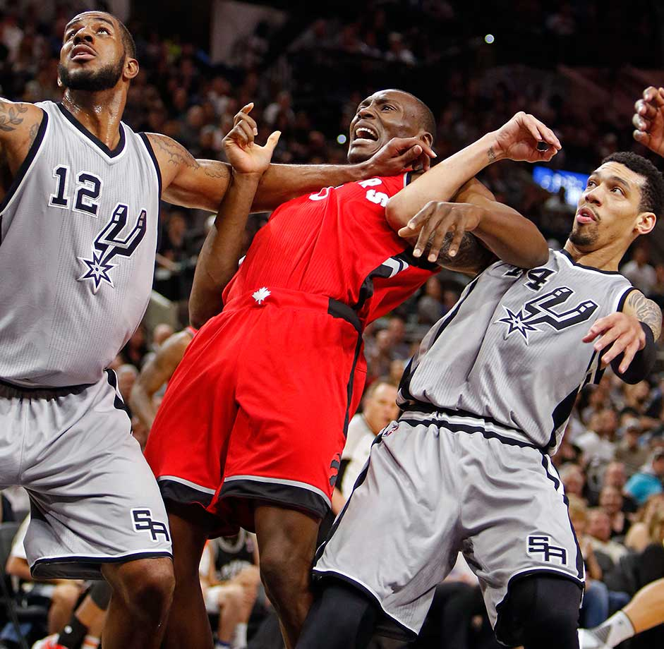 San Antonio forward LaMarcus Aldridge strong arms Bismark Biyombo out of the way while vying for a rebound.