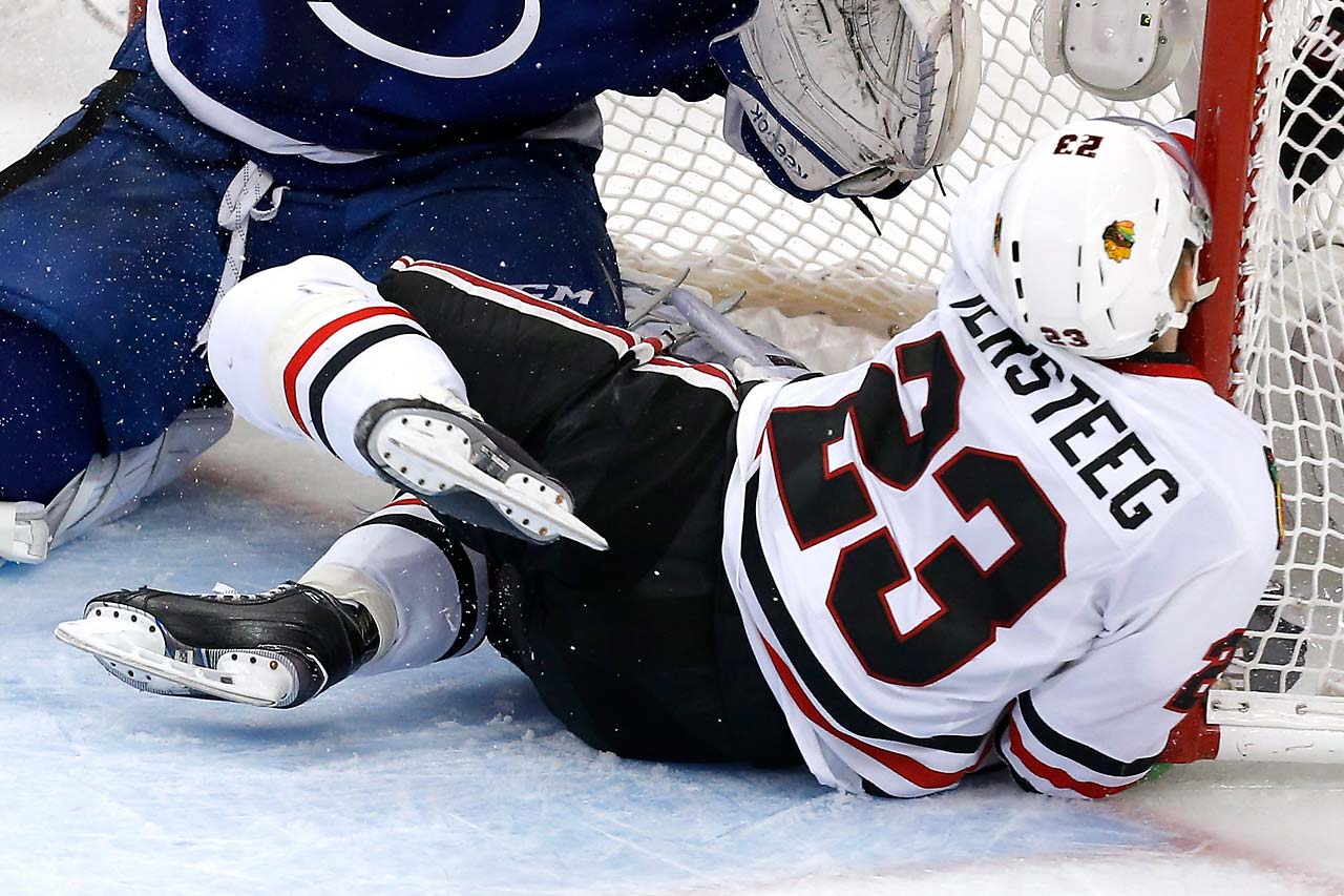 Kris Versteeg of the Blackhawks crashes into the net against Ben Bishop.