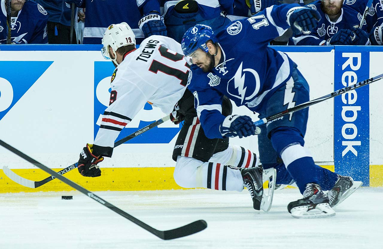 Jonathan Toews of the Blackhawks collides with Ville Pokka of the Lightning.