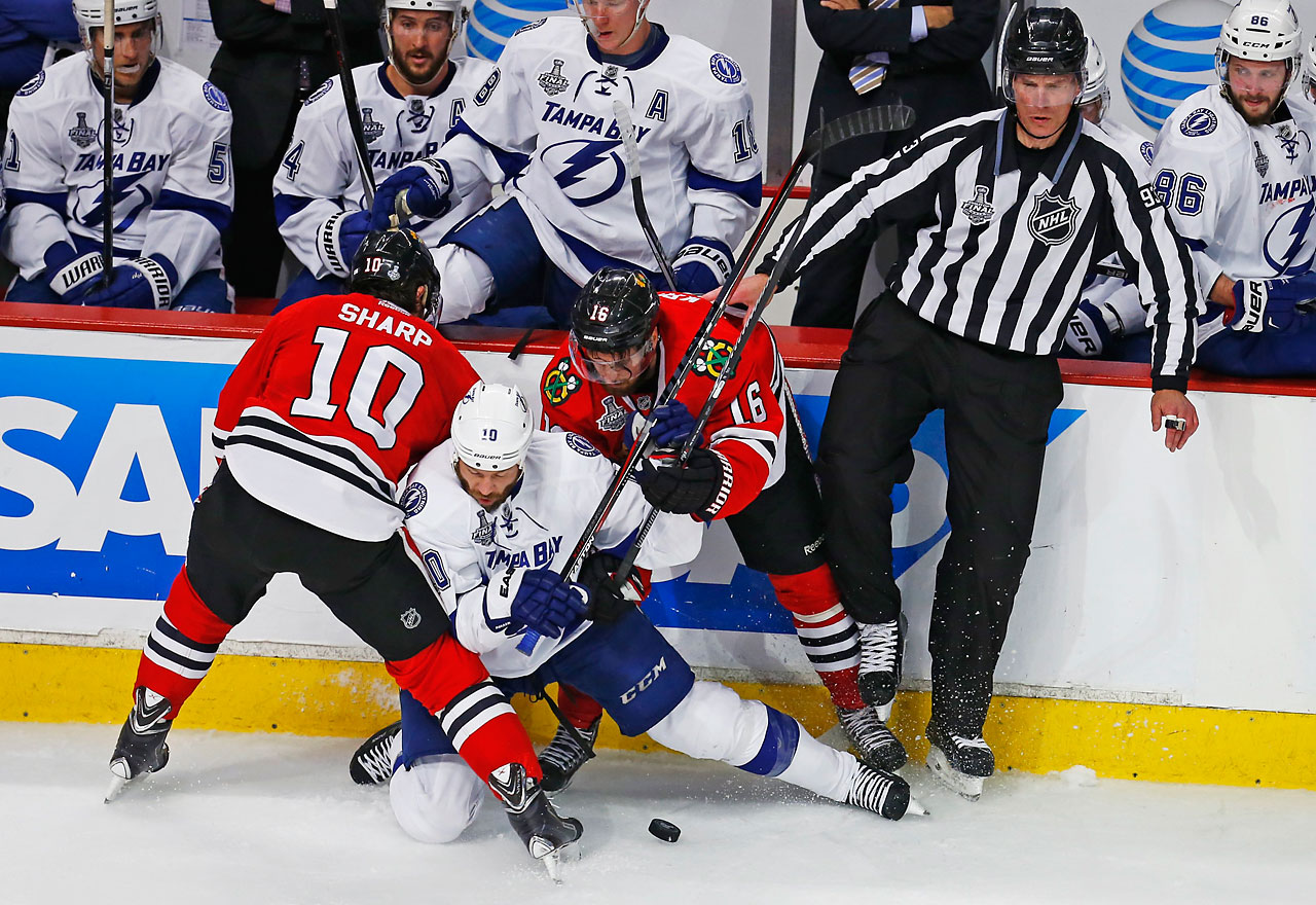 Brenden Morrow of the Lightning falls between two Blackhawk defenders as he attempts to control the puck.