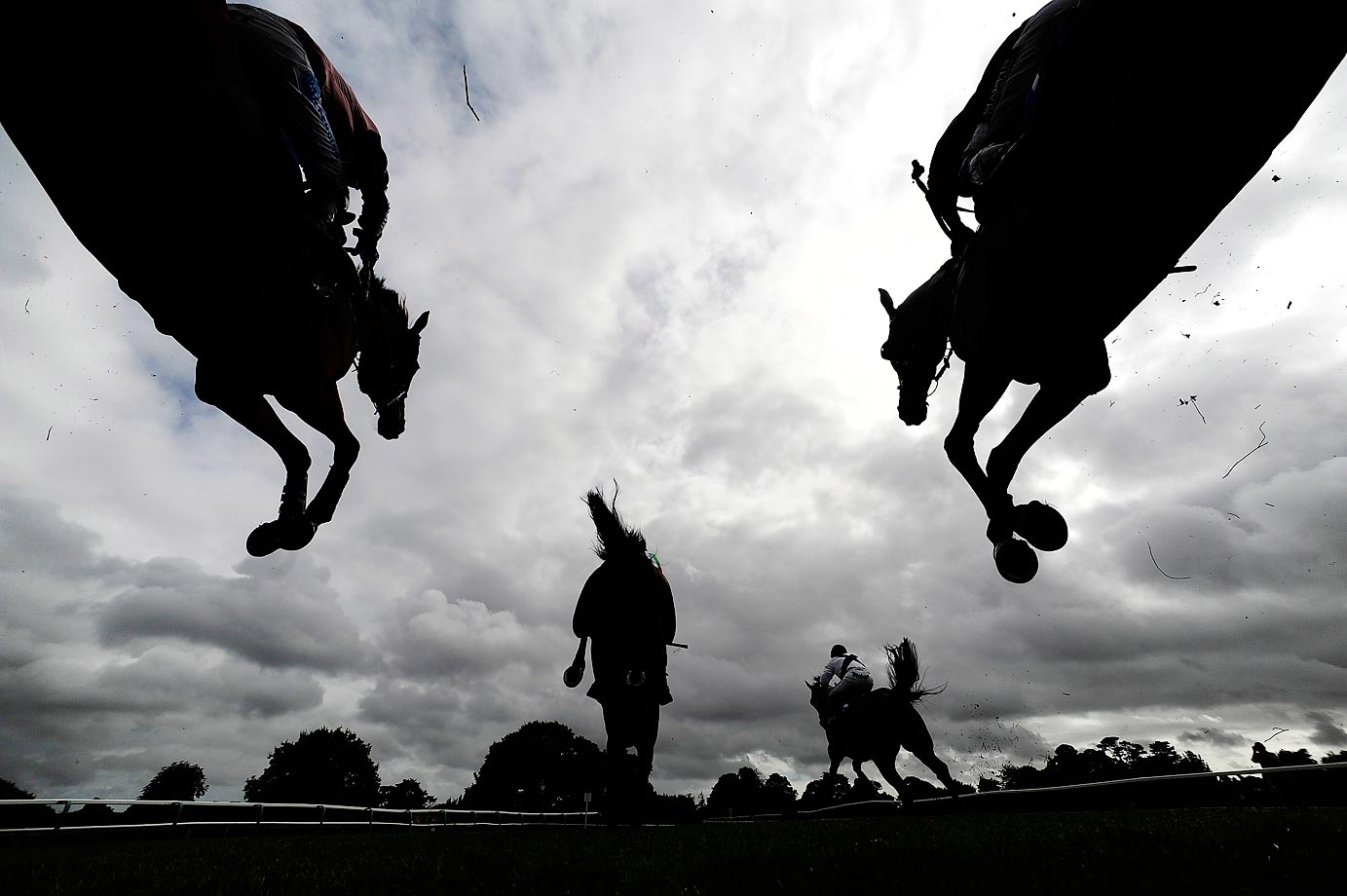 Competitors clear a fence in The £500 Permanent Money Backs Handicap Steeple Chase at Fontwell racecourse on Aug. 28.