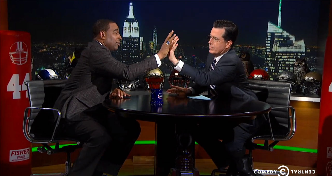 Cris Carter compares hand sizes with Stephen Colbert on The Colbert Report on Jan. 29, 2014 in New York City.
