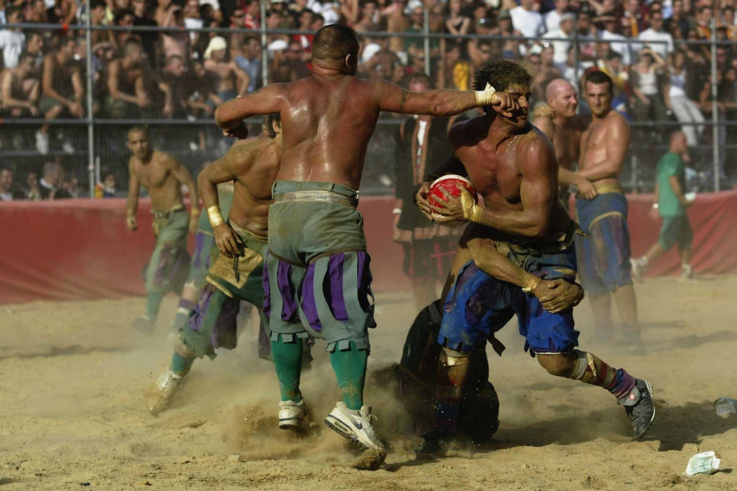 The Verdi and Azzurri teams fight for the ball during the Calcio Fiorentino, a medieval football event held between the four quarters of Florence since 1584 at La Piazza Santa Croce in Florence, Italy.