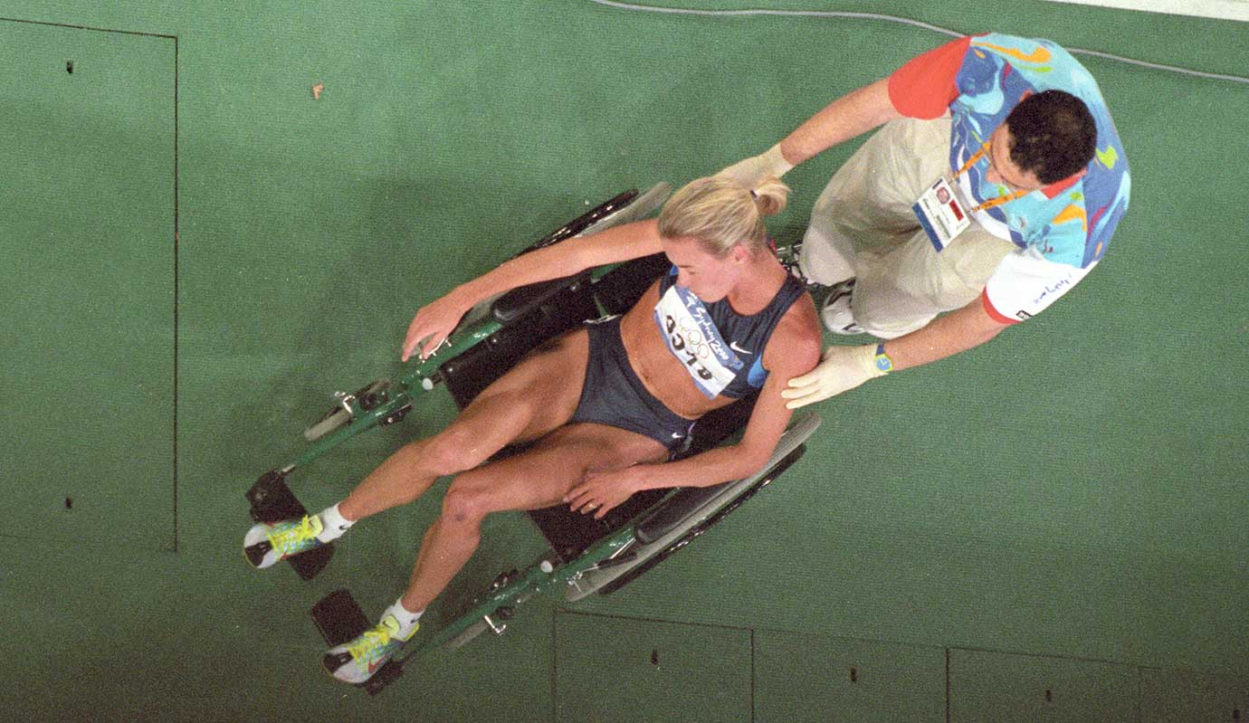 Suzy Favor Hamilton is helped off the track after falling during the 1,500-meter final at the 2000 Olympics in Sydney, Australia.