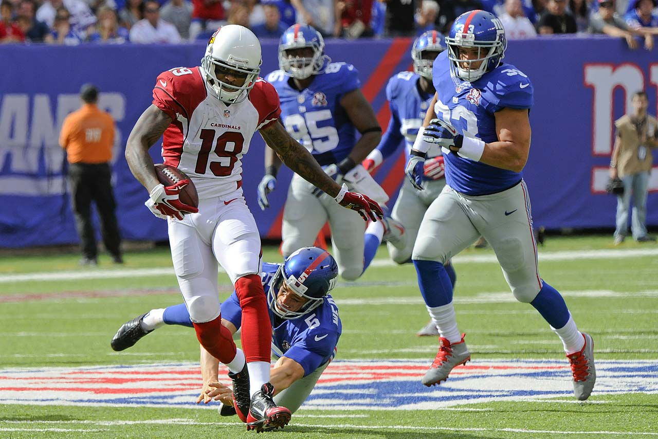 Arizona's Ted Ginn breaks a tackle by Steve Weatherford of the Giants on his way to a 71-yard punt-return touchdown.
