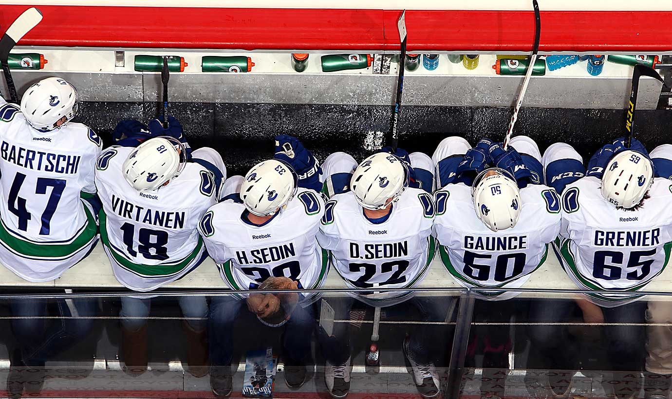 Vancouver Canucks players look on from the bench during a game against the Winnipeg Jets.