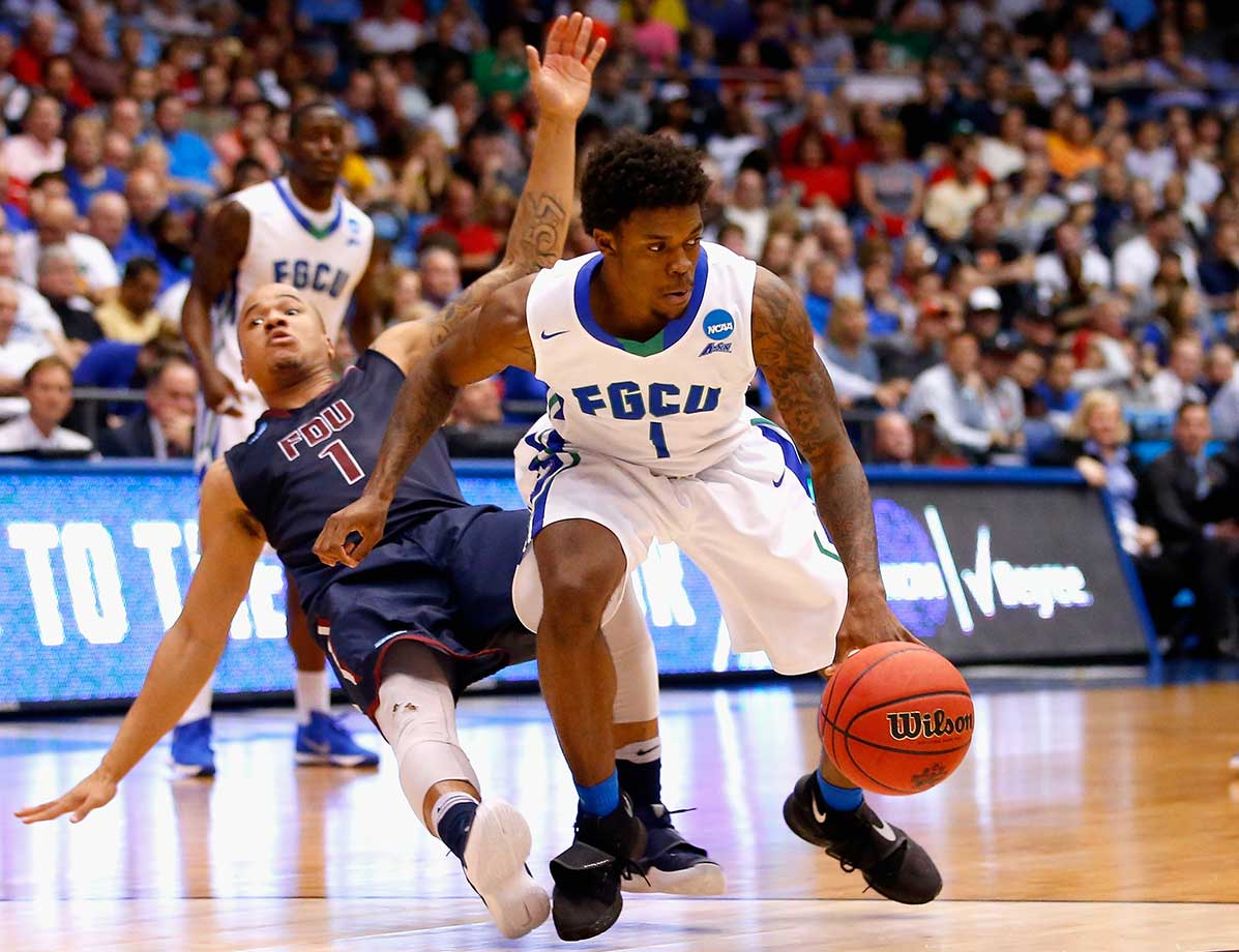 Stephan Jiggetts of Fairleigh Dickinson falls as Reggie Reid of Florida Gulf Coast handles the ball.