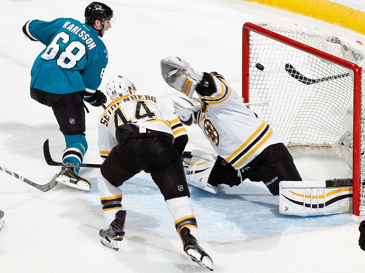 Melker Karlsson of the San Jose Sharks scores against Tuukka Rask and Dennis Seidenberg of the Boston Bruins.