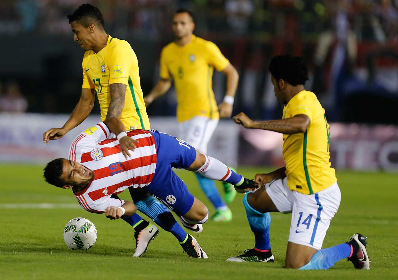 Dario Lezcano of Paraguay falls as he fights for the ball with Luiz Gustavo and Gil of Brazil during a World Cup qualifying match.